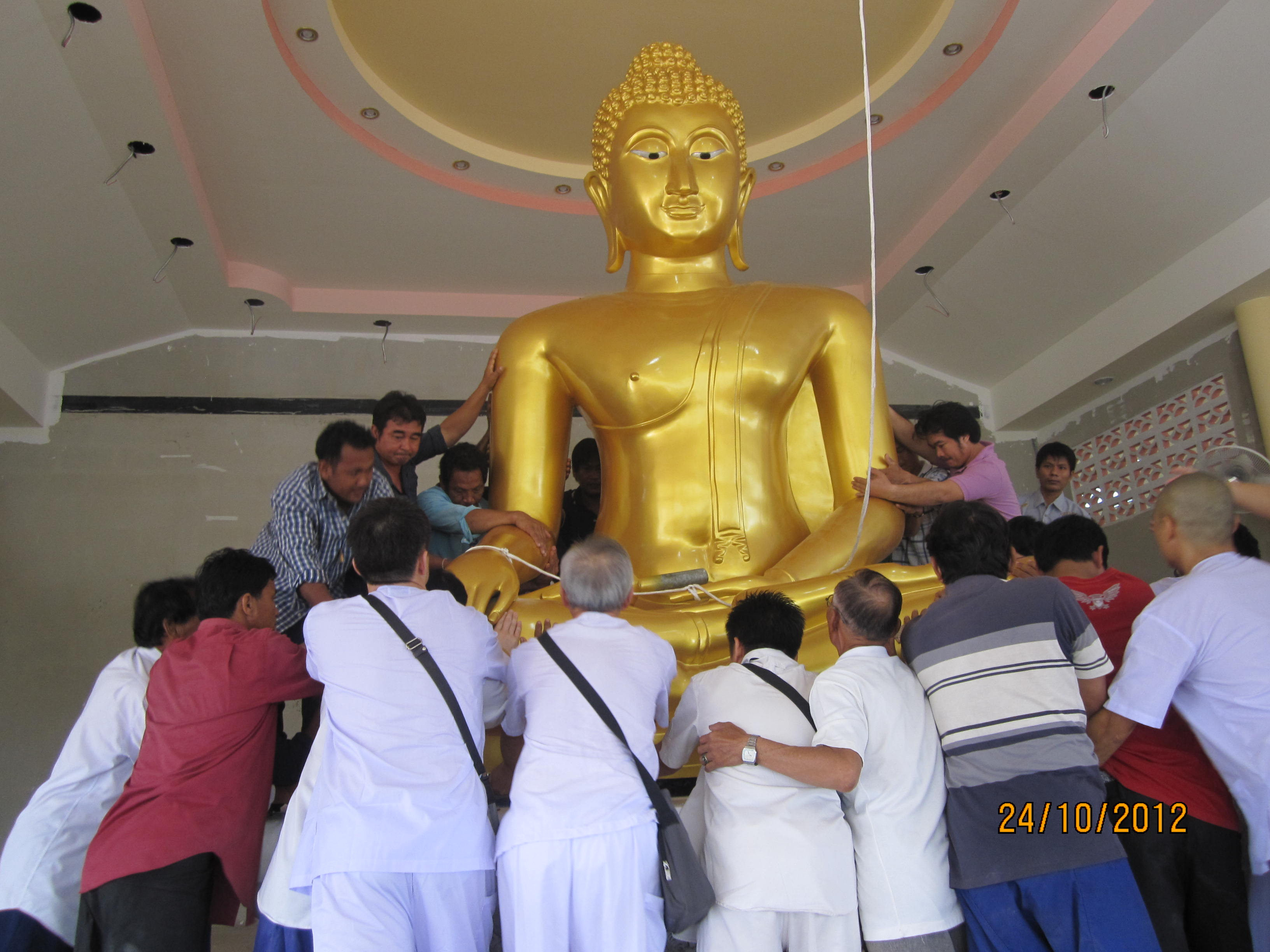 Male followers helping to move the Buddha statue to the Shrine Hall